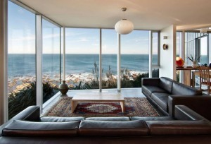 enchanting-living-room-design-with-wide-glass-window-view-ocean-plus-rug-under-wooden-table
