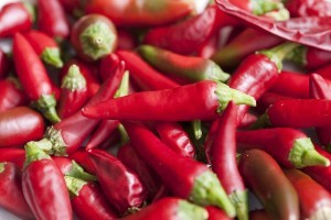 Background of fresh red hot chili peppers, or cayenne chillis, a pungent strong flavoured spice used in cooking