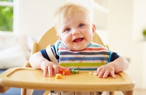 child-in-high-chair-eating-fruit