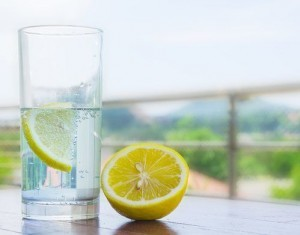 Glass of water with lemon isolated on white background